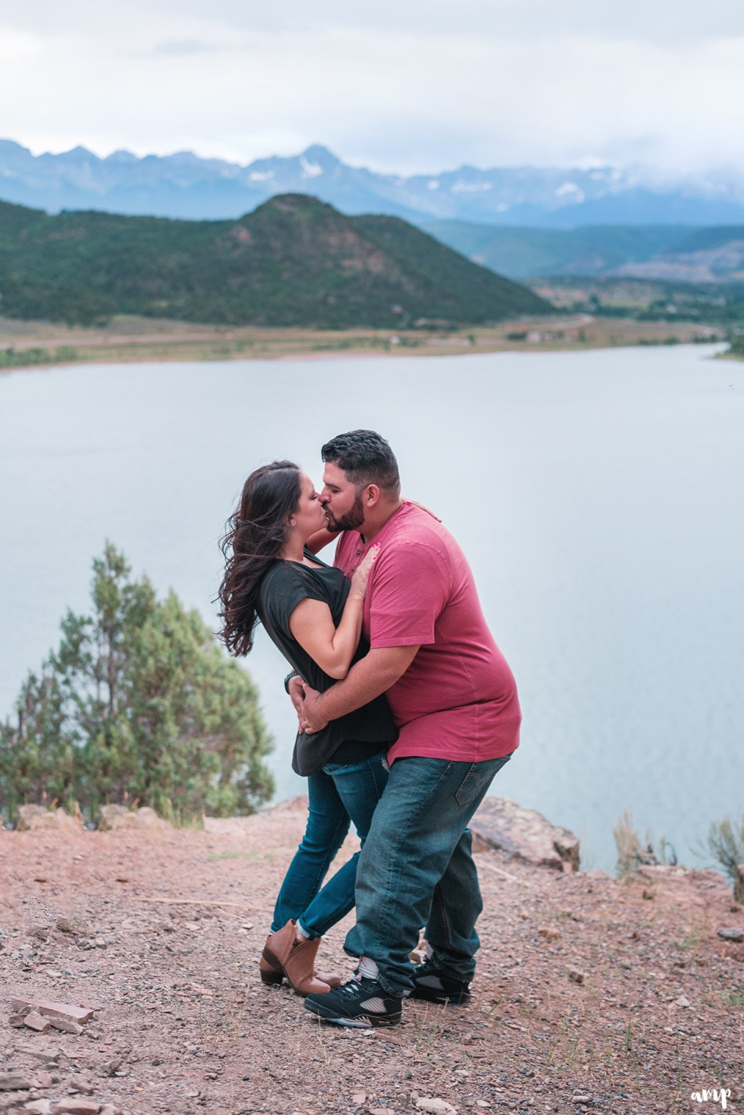 Engaged couple kissing overlooking the San Juan Mountains