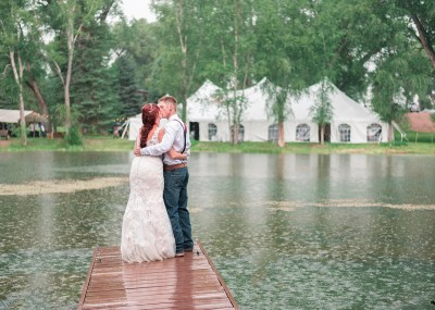 Bride and groom kissing on the dock of a pond with wedding in background