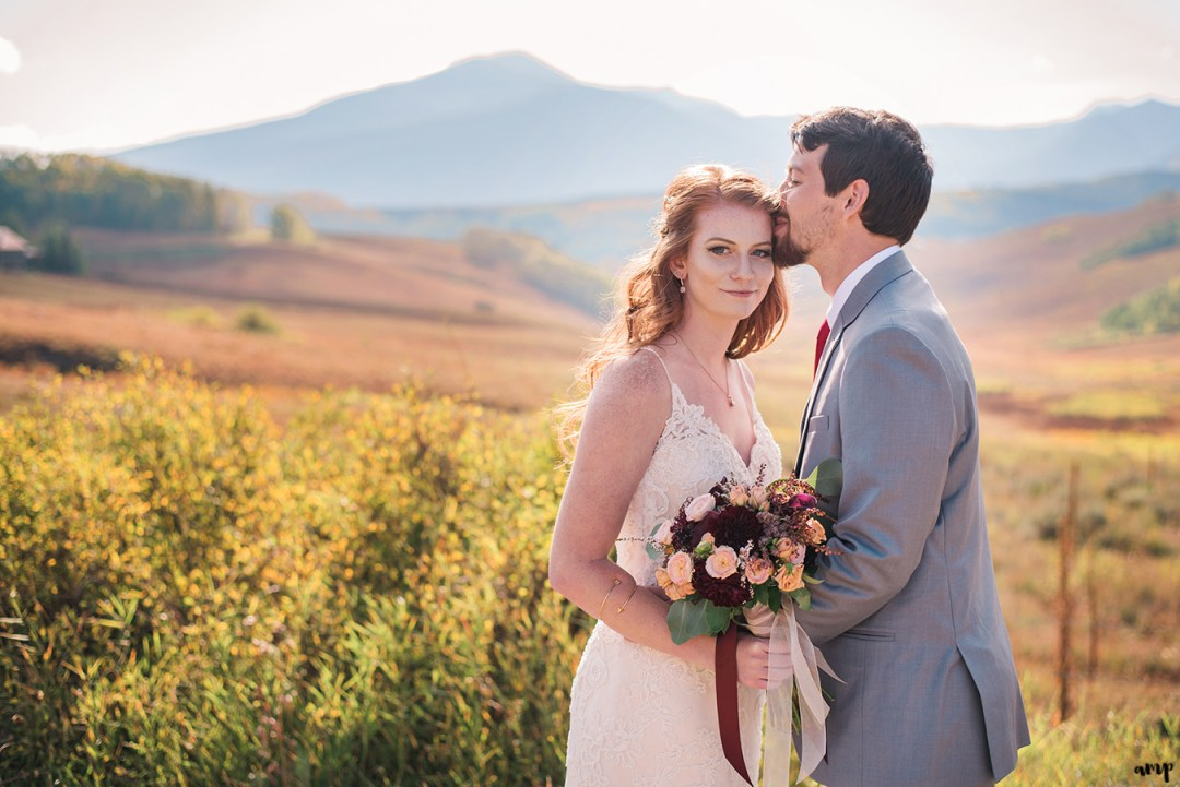 Bride and groom snuggling among the fall colors with mountains in the background