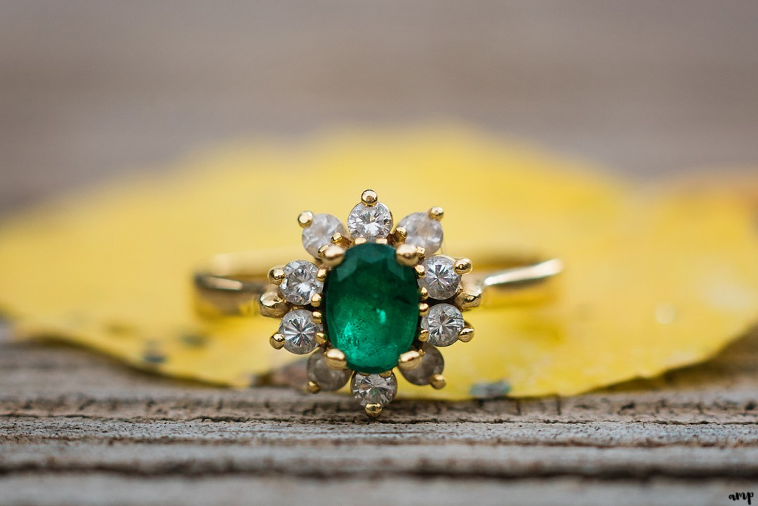 Emerald and diamond engagement ring on an aspen leaf