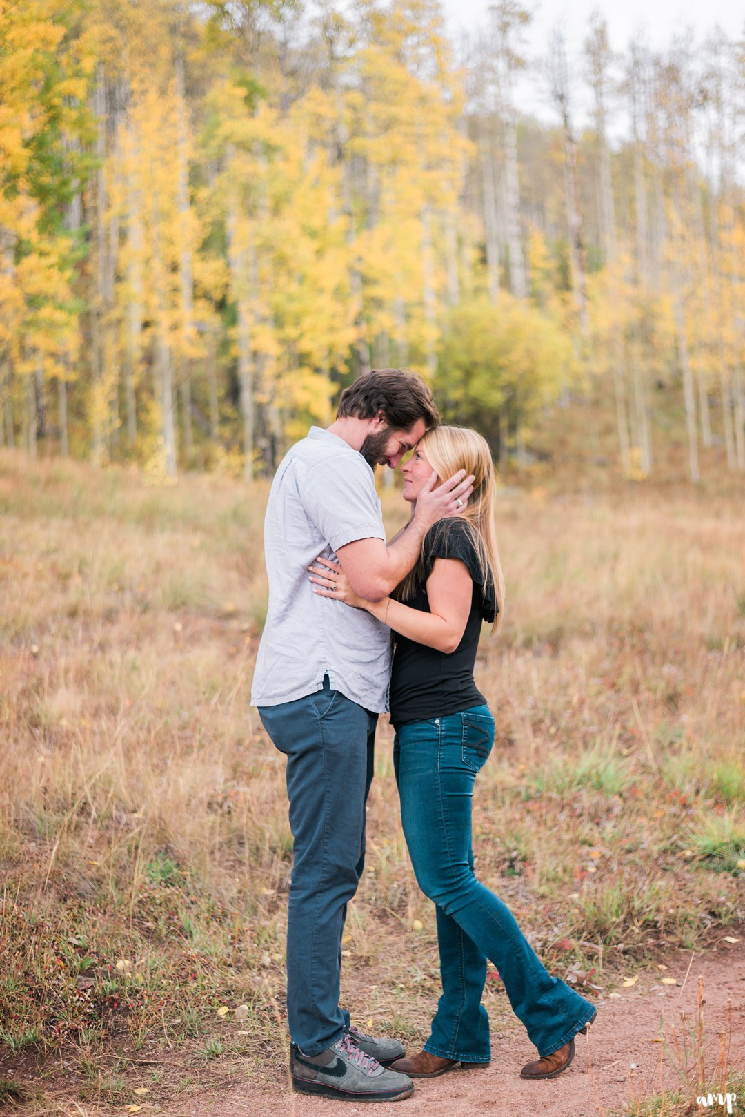 Engaged couple kissing in the fall leaves at Piney River Ranch in Vail