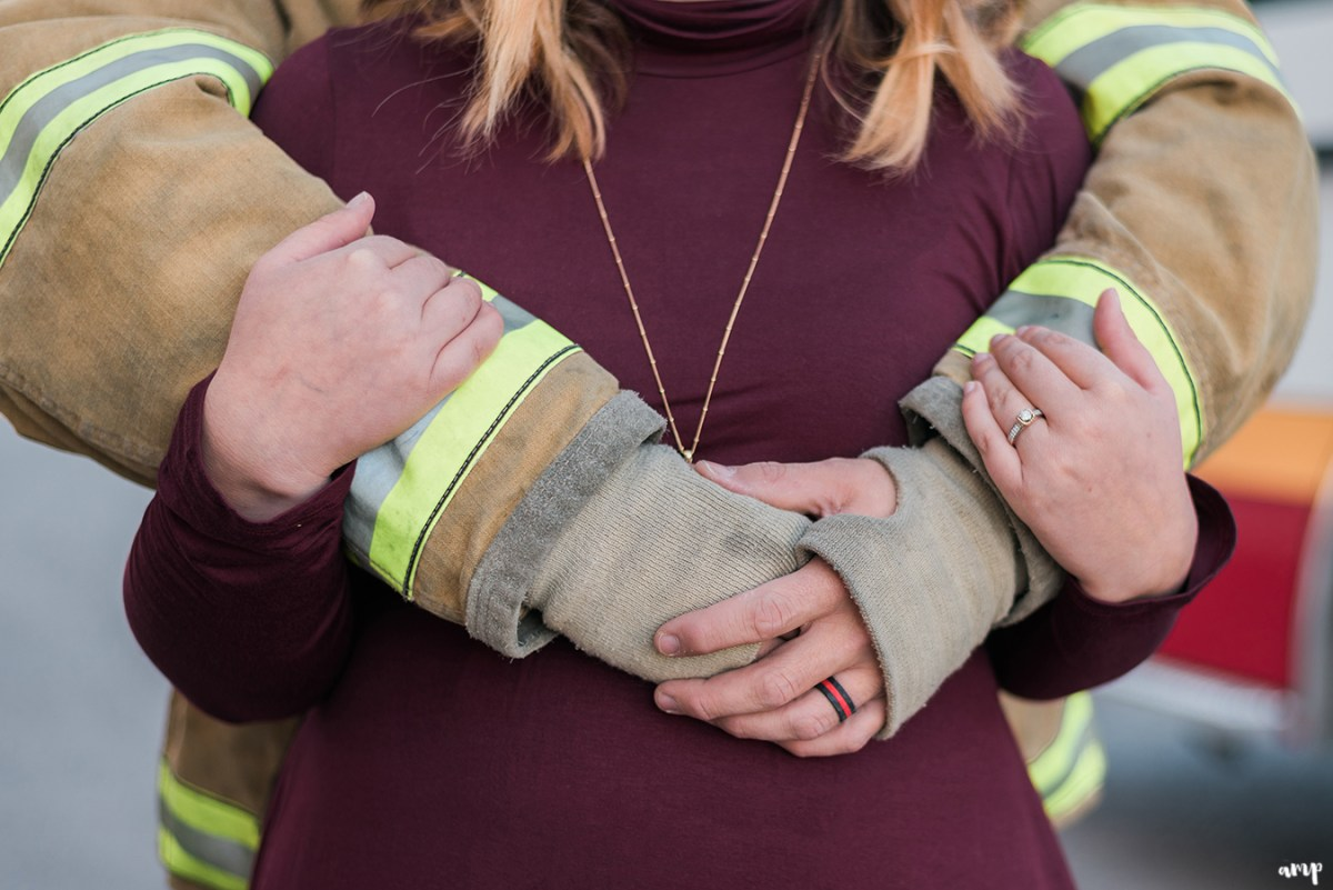 Firefighter and firefighter's wife cuddling, showing off the rings