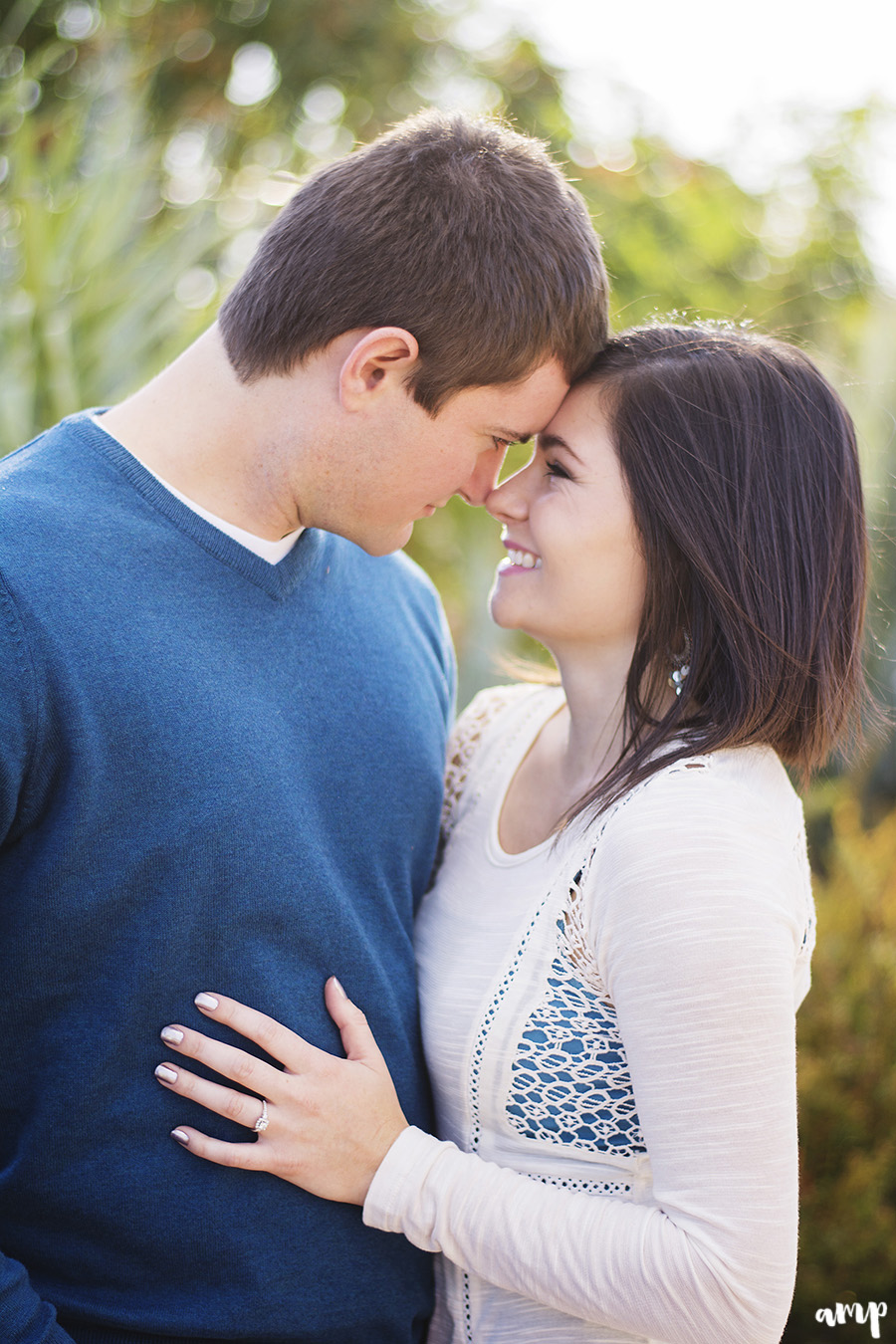 Engaged couple forehead to forehead, showing off her ring on his chest