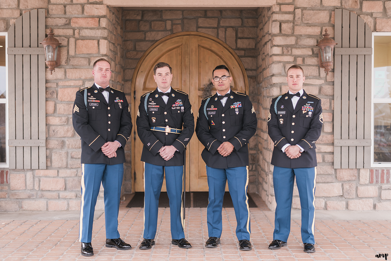 Groomsmen dressed in Army blues pose in front of the doorway of the vineyard at Two Rivers Winery