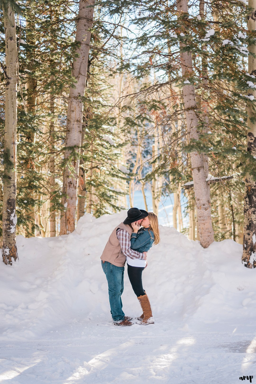 Engaged couple kissing beneath snowy pine