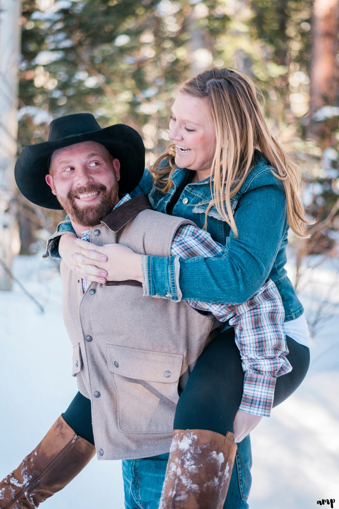 Engaged couple in piggy back ride laughing at each other