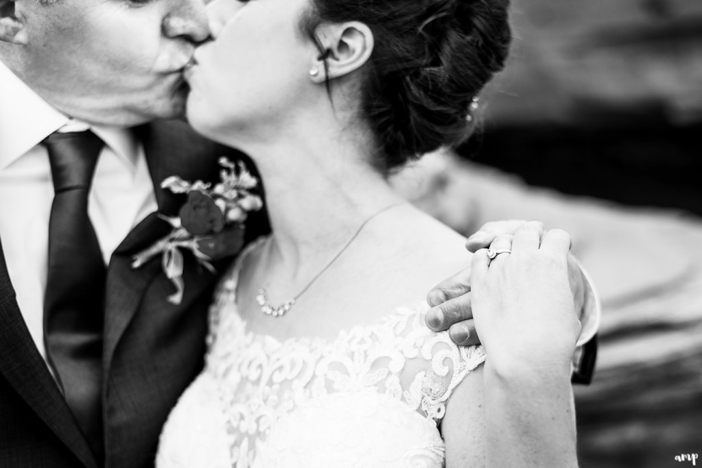 Black and white photo focused on wedding rings while couple kiss