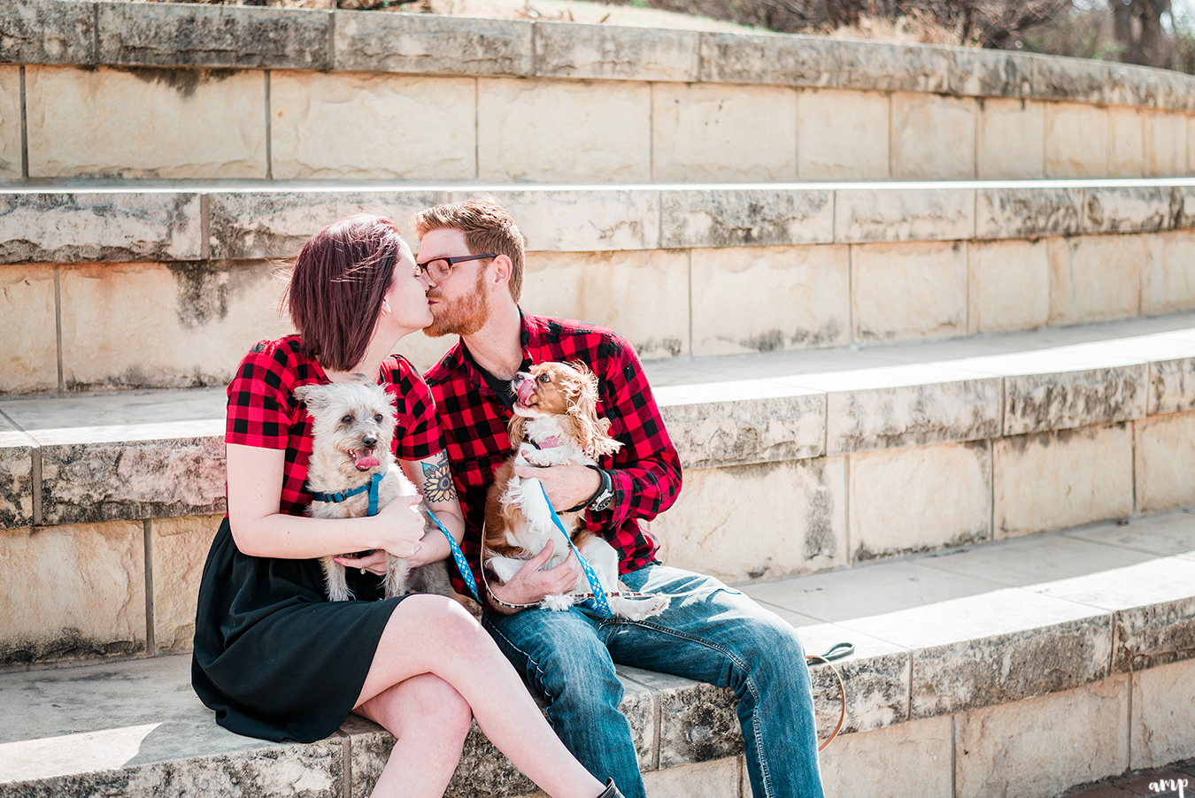 Ben and Courtnee kiss while holding their dogs along the riverfront