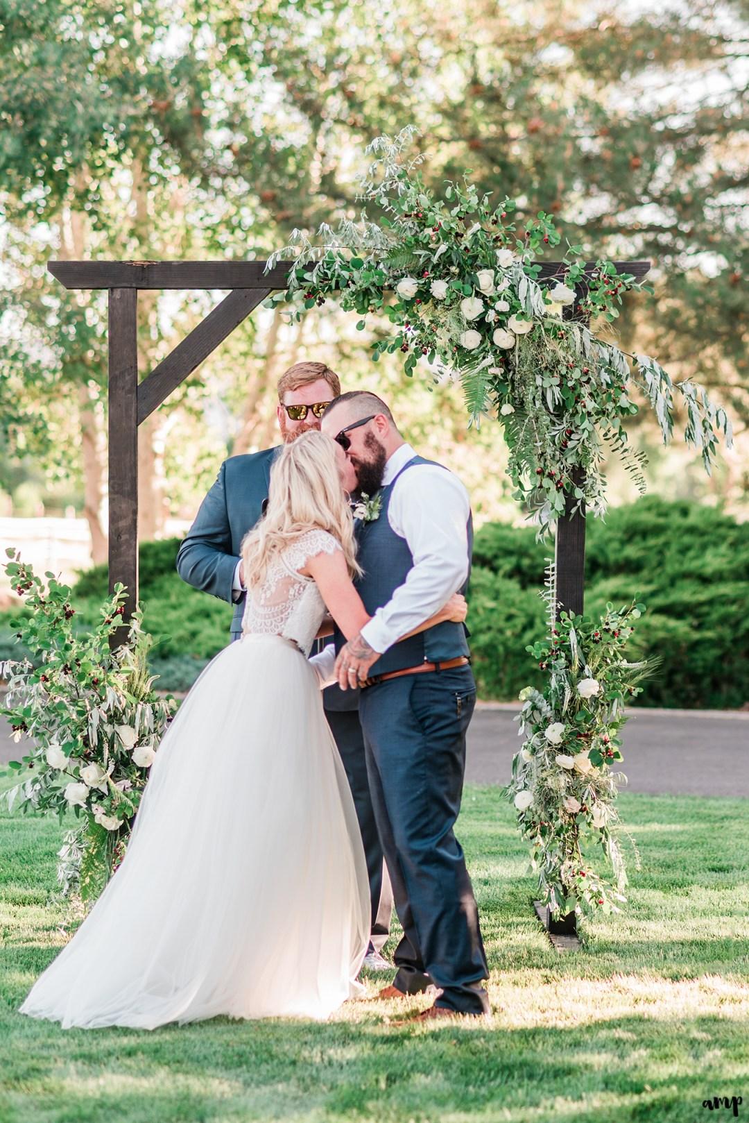 Beth and Dustin's first kiss | Grand Junction Backyard Wedding | amanda.matilda.photography