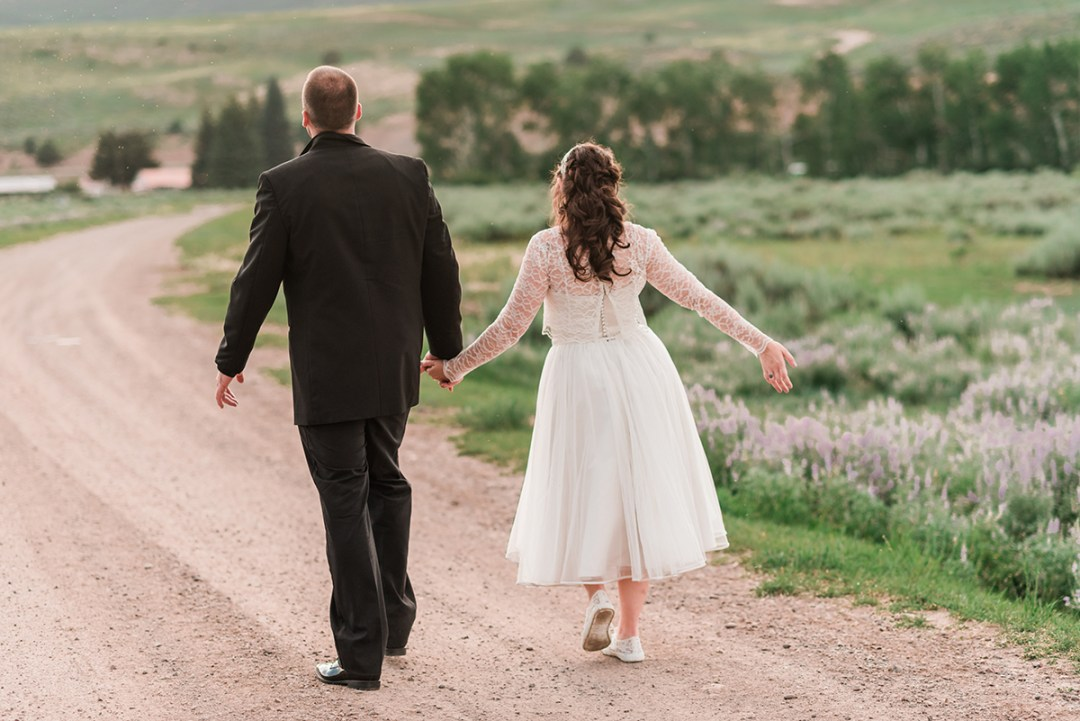 Bride and groom walking down a dirt road at sunset at Rolling R Ranch near Meeker