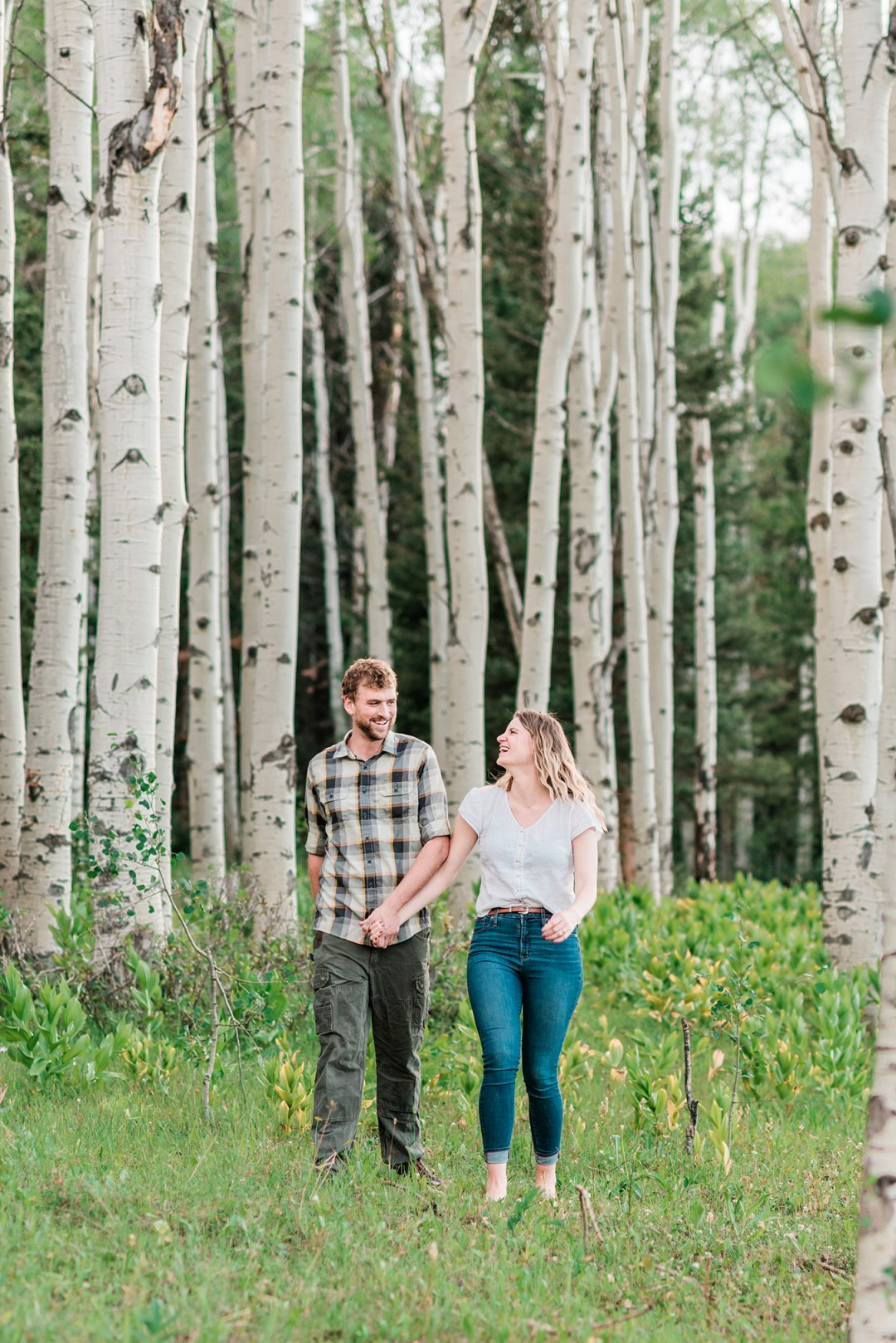 Annie & Taylorwalk through an Aspen glen for their Glenwood Springs Engagement Photos