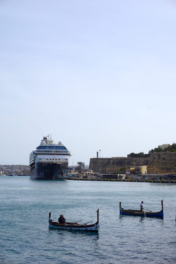 Traditional Maltese boats in the Grand Harbour with a cruise ship behind