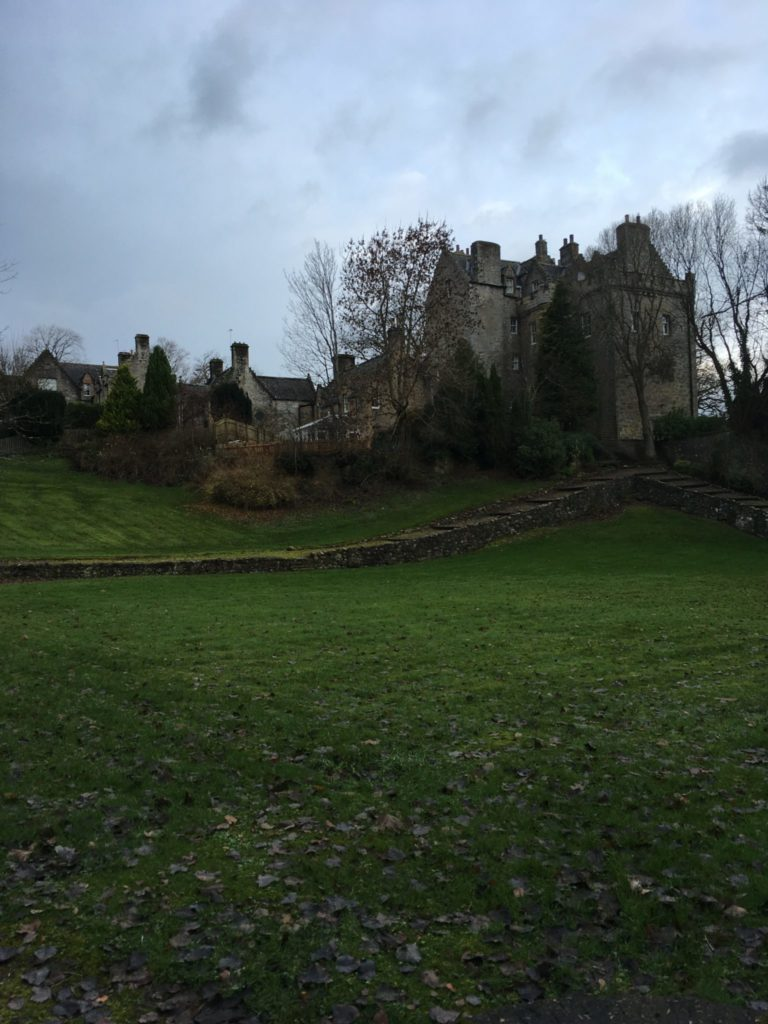 In Edinburgh, a large grassy lawn leading to an old castle partially seen behind various trees.
