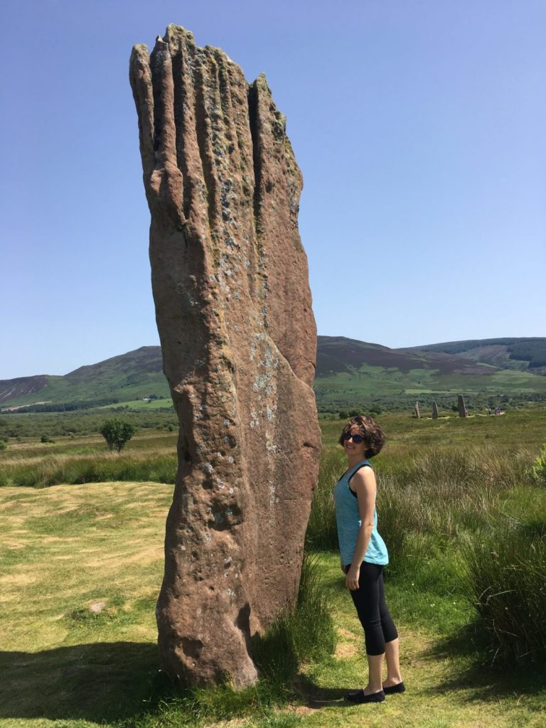 Amanda Walkins in front of a large standing stone on Arran Scotland