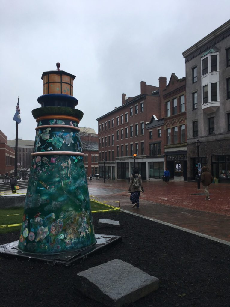 Small lighthouse statue in a pedestrian area of Portland Maine