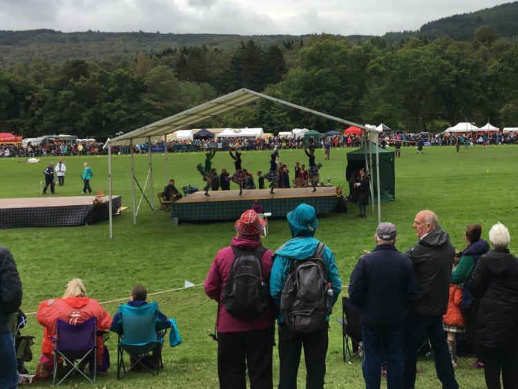 Highland dancers on a covered stage at the Pitlochry Highland Games