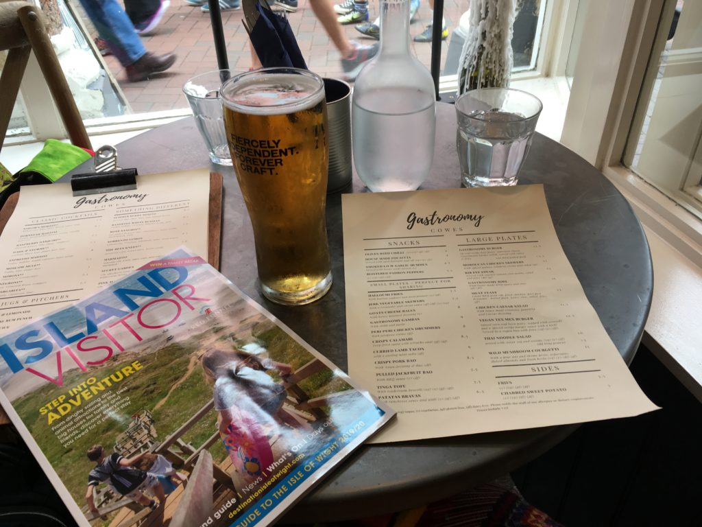 table setup at Gastronomy restaurant in Cowes on the Isle of Wight with Island Visitor magazine and a beer