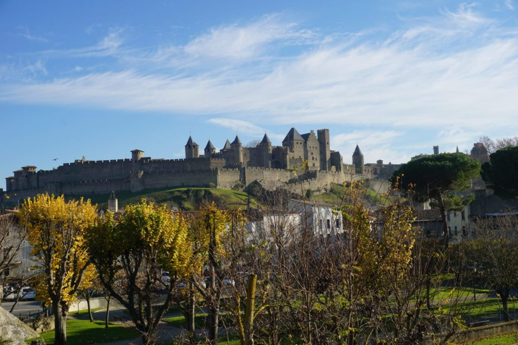 Blue sky over the castle in Carcassonne in winter with yellowing trees in the foreground