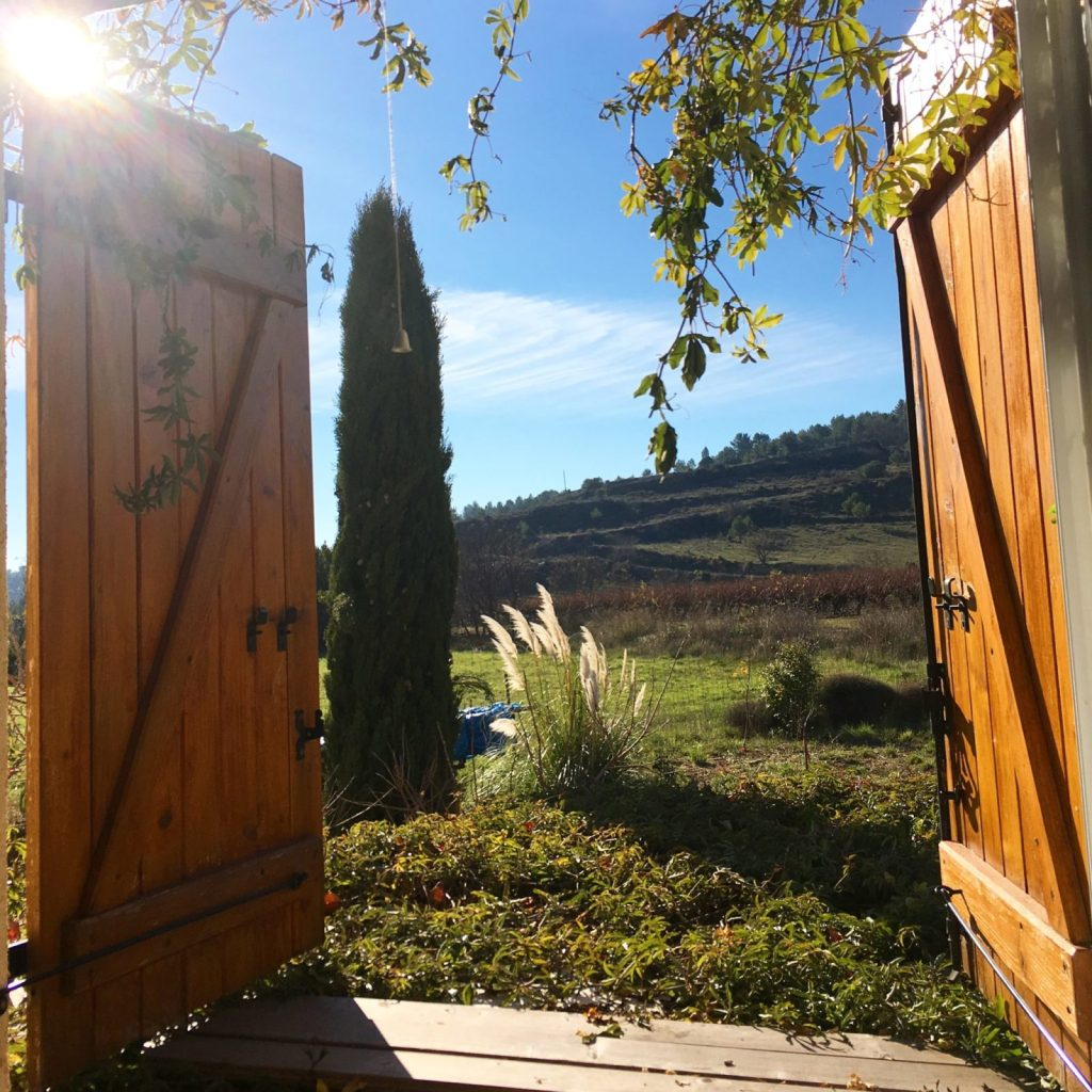 wooden shutters open onto the vineyards and landscape filled with sunshine in southern France in December