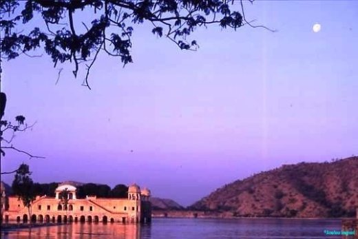 Lake pavilion, Amber, Jaipur. At dusk, with a small moon rising, the sandstone pavilion with small cupolas at each corner sits in a lake, glowing with the ochre rays of the just departing sun