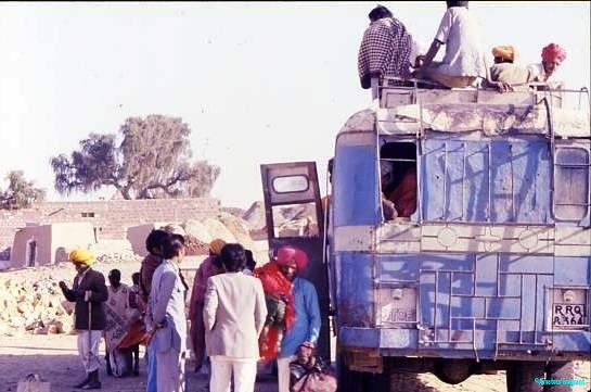 Village bus, Rajasthan. A very rickety blue bus stops for a small crowd of passengers - at least four further passengers ride on the roofrack