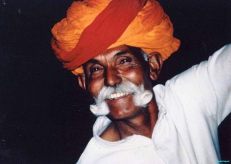 An elderly Indian man with large moustaches grins with eyes sparkling beneath a large orange and rred turban