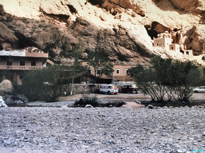 Two VW campers parked in front of a hotel at the foot of a huge rock wall