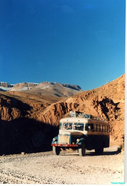 An ancient bullnosed bus climbs on a dirt road from a deep gorge. A dusting of snow lies on the mountaintops a few miles distant