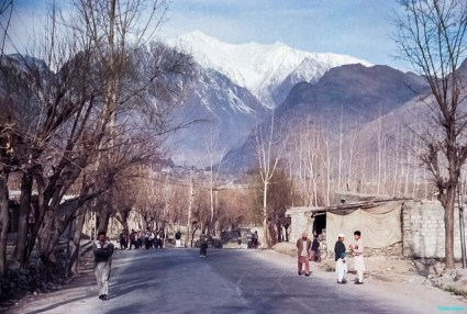 A village street with little traffic. Lined with Poplars, with typical fishbone outline in winter and single storey buildings. The village is dwarfed by the enormity of snow-capped peaks beyond in northern Pakistan