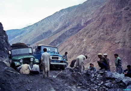 On a mountainside in northern Pakistan a group of men dig and toss stones around to form some sort of passable roadbed that vehicles can use after a landslide destroyed the old road