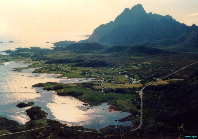 Scattered homesteads sprinkle the coastal strip, flanked by high mountains