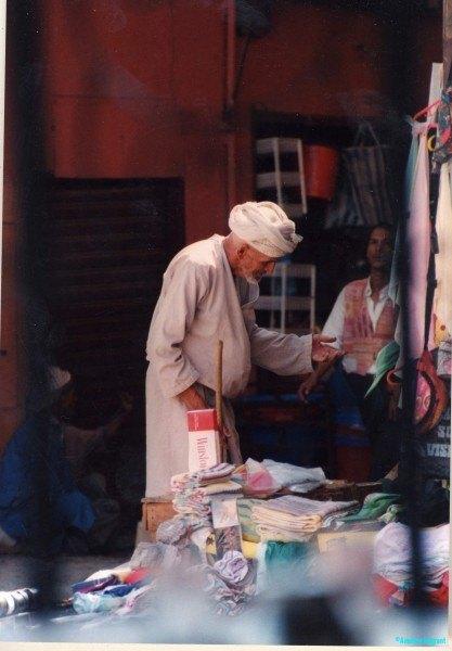 An elderley man calls by at a merchant's stall
