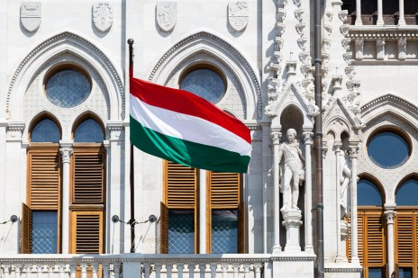 a close up of the HUngarian flag with the Parliament building in the background.