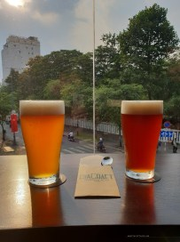 two beers - one golden the other dark amber - on a window seal with a view of a busy Vietnamese road below.