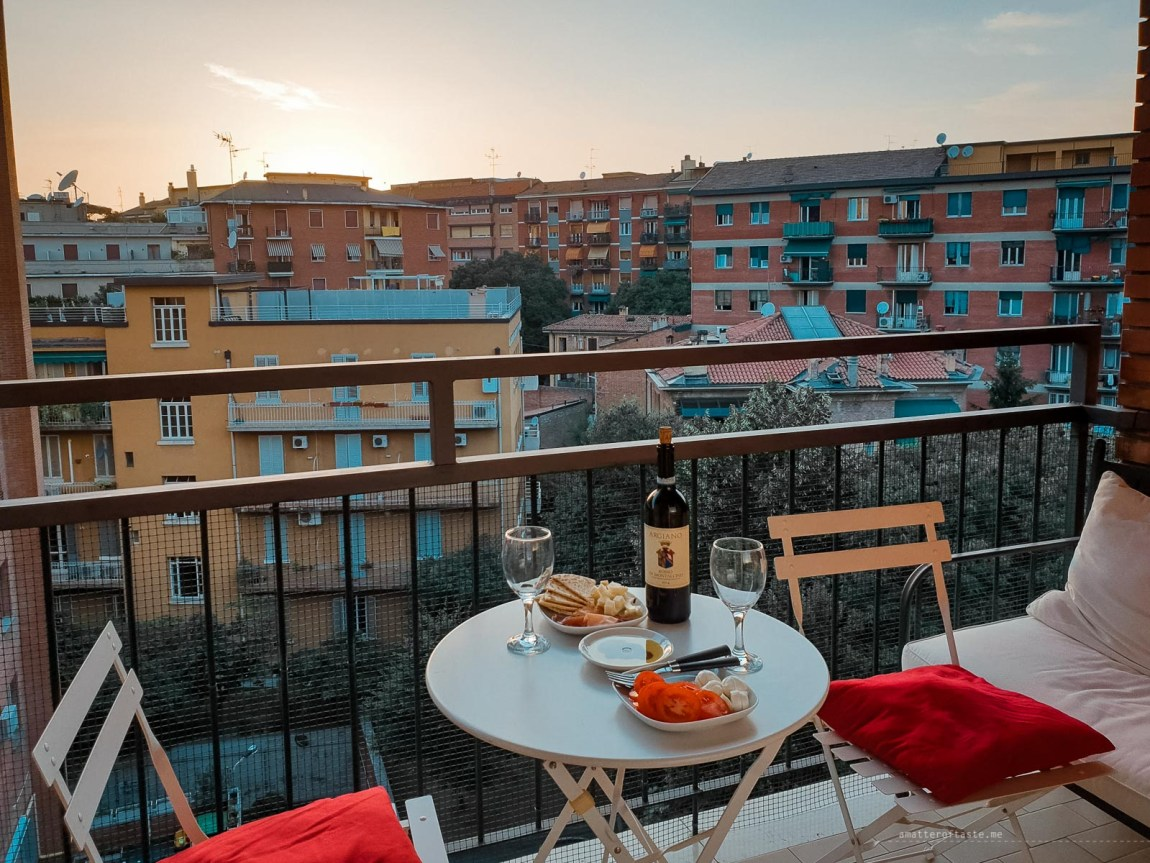 Balcony with white chairs and a small round table and a lovely sunset in the background. There is food and wine on the table of course.