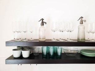 Two open shelves filled with wines glasses, mugs and bowls. A kind of useful kitchen feature that is also decorative.