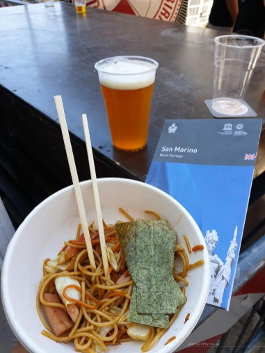 A bowl of yakisoba, a cup of craft beer and a map of San Marino.