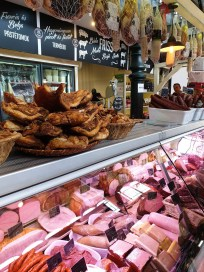 A fridge display of meats, sausages, hams and salamis at a local market stall. On top of the fridge are small buckets full of crackling.