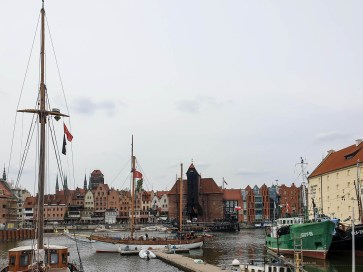 Gdansk Old Town seen from across the river. There is a small marina in the front and the old town with the famous crane in the background.