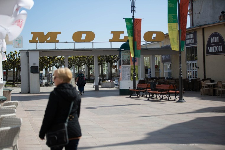 """my mum standing in front of the old school sign """"Molo"""" at the Sopot pier."""