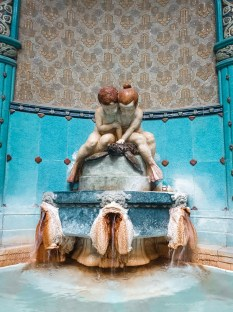 A cute sculpture of boy and girl sitting atop a fountain fetured in one of the hot thermal baths.
