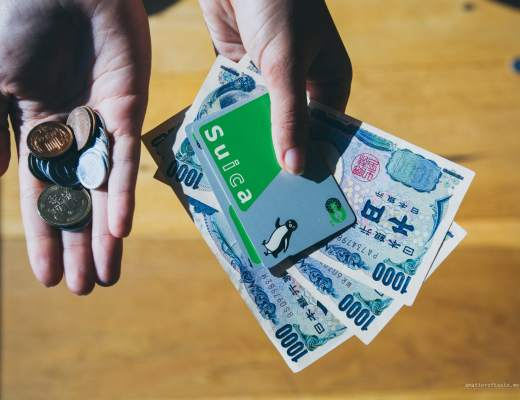 How much does it cost to travel in Japan illustrated with hands holding Japanese yen. There are coins in one hand and banknotes with IC Suica card on top in the other.