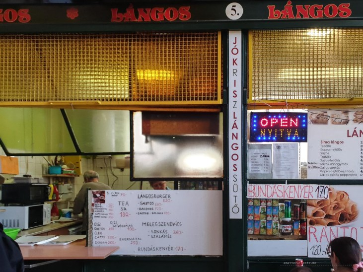 the shop-front of the langos place at the Rakoczi Market.Yellow-stained glass, overall retro feel and hand-written menu.