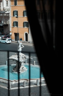 view from the window - a baroque fountain standing in the middle of a sun-flooded square.