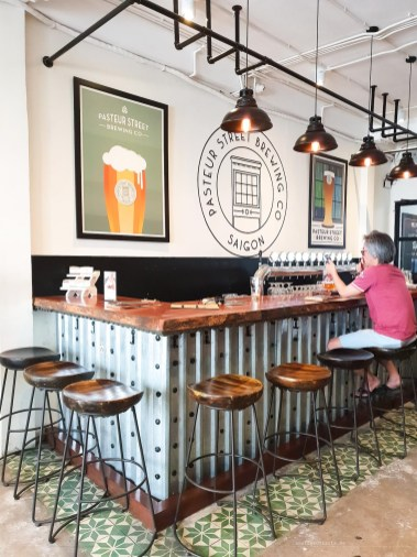 Inside the Pasteur Brewing Company taproom. A metal, industrial-looking bar with one person sitting on a high stool and drinking beer.