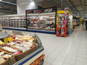A cheese and meat alley in my local Tesco shop. There are many salami sausages hanging there.