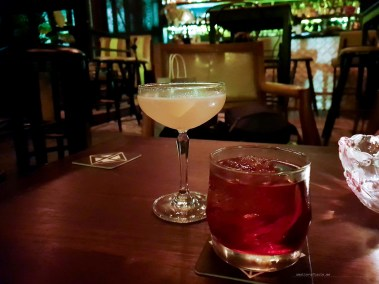 Two fancy cocktails in a dimply lit bar.