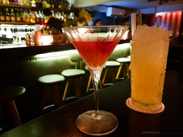two cocktails on a table - red one in a martini glass and yellow in a tall glass.