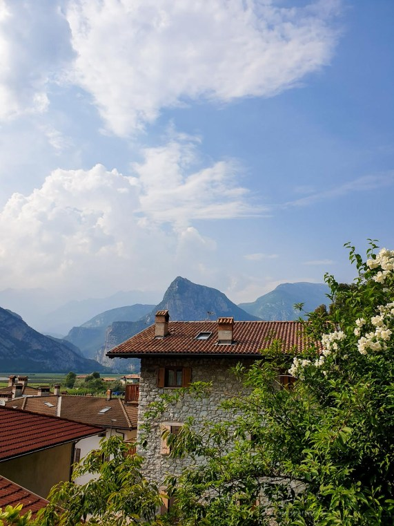 Idyllic image of flowers, stone-made houses and mountains in the background on a perfect sunny afternoon.
