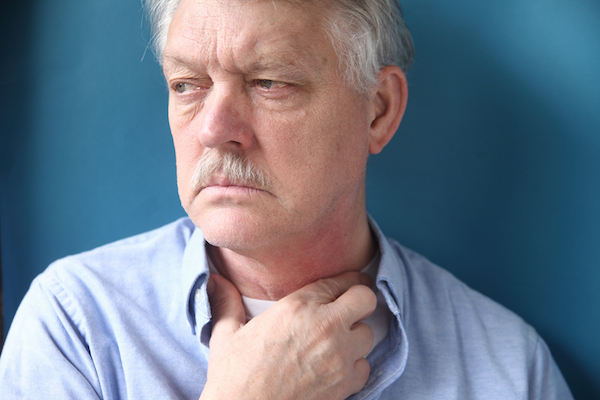 Businessman with hand at throat